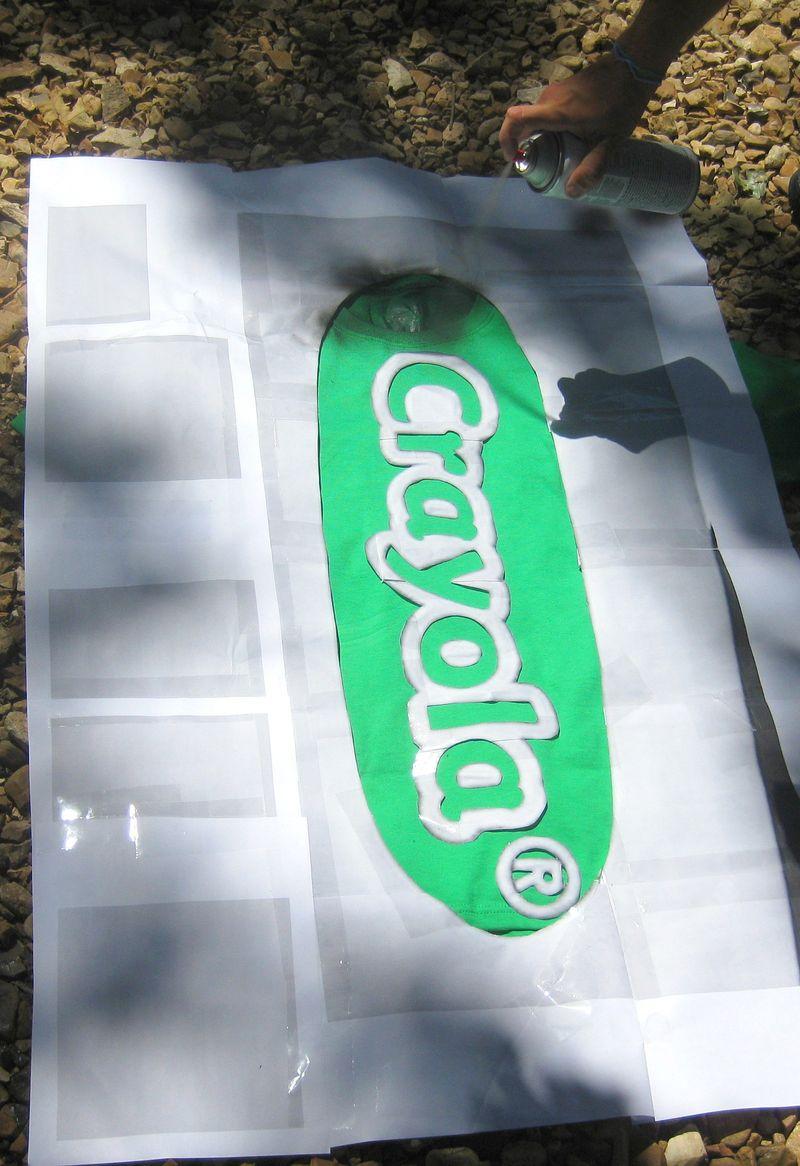 Spray painting a logo onto a t-shirt costume